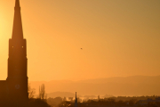 Uranienborg kirke, men nå med en fugl i solnedgangen